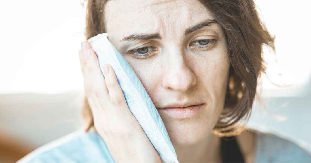 Woman wearing a light blue shirt holding an ice pack on her face to calm swelling down after a dental injury.