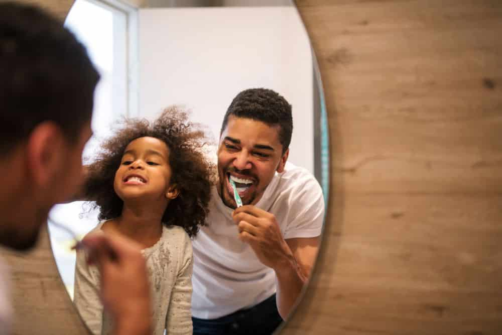 African american girl brushing teeth with dad.
